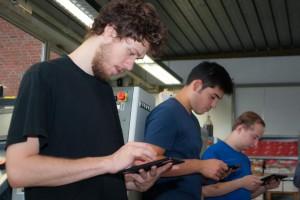Drei Lernende mit Tablets in einer Reihe