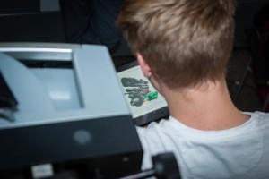 Lernender neben Maschine mit geöffneter Lernanwendung